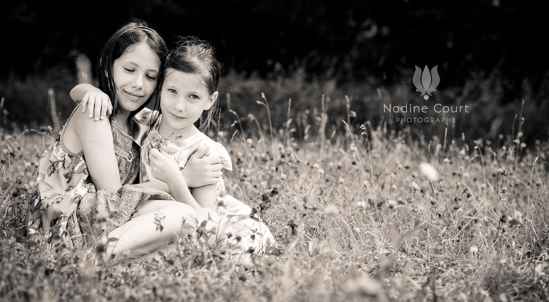 Portrait d'enfant : 2 soeurs assise dans un pré fleuri